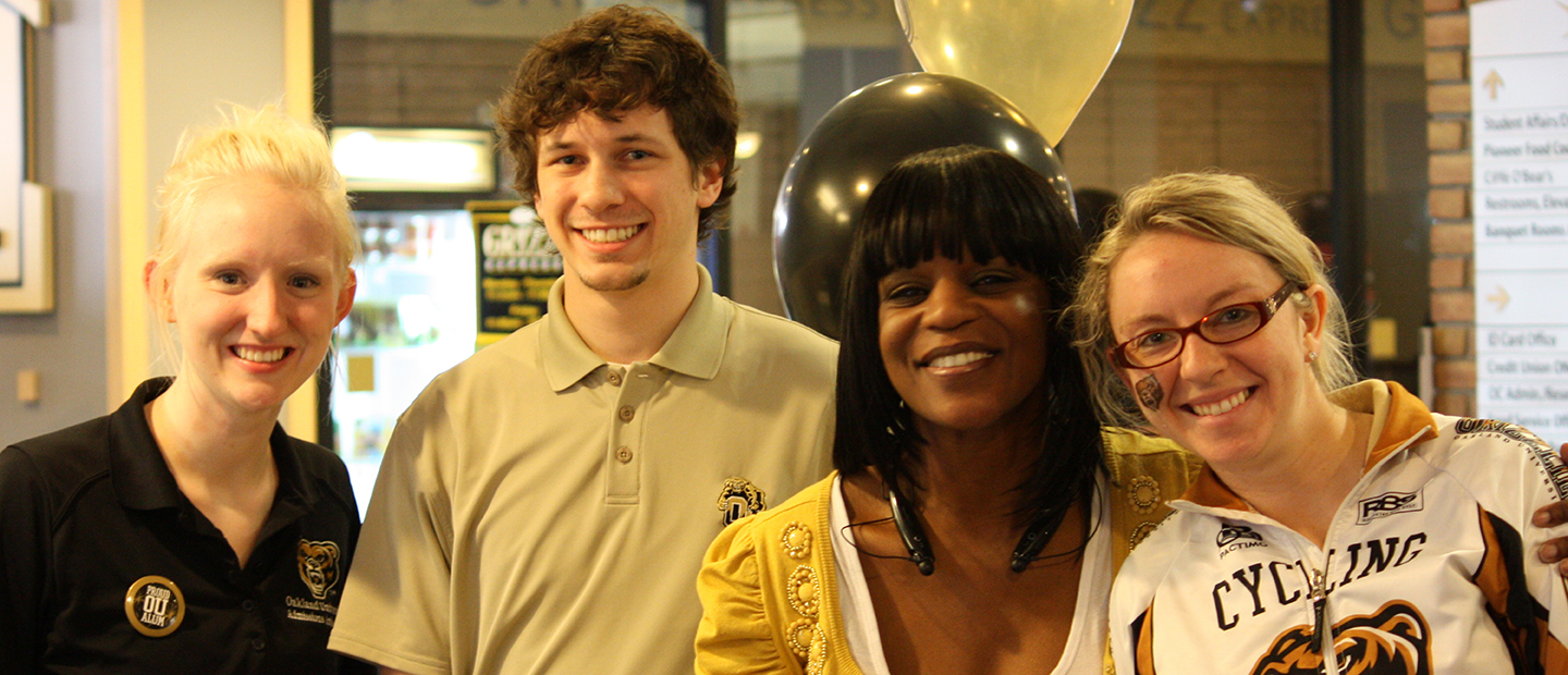 four people wearing black, white and gold in an office with balloons behind them