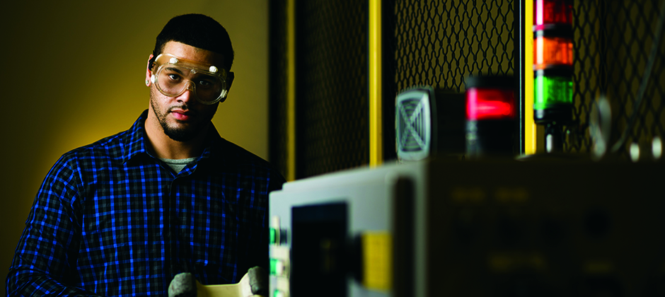 young man wearing safety glasses working on mechanical equipment