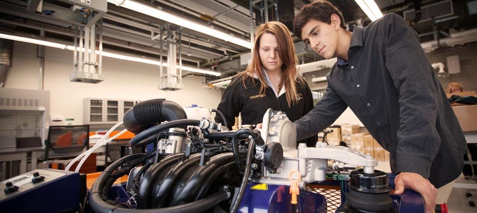 Male and Female students working on the engine of a race car