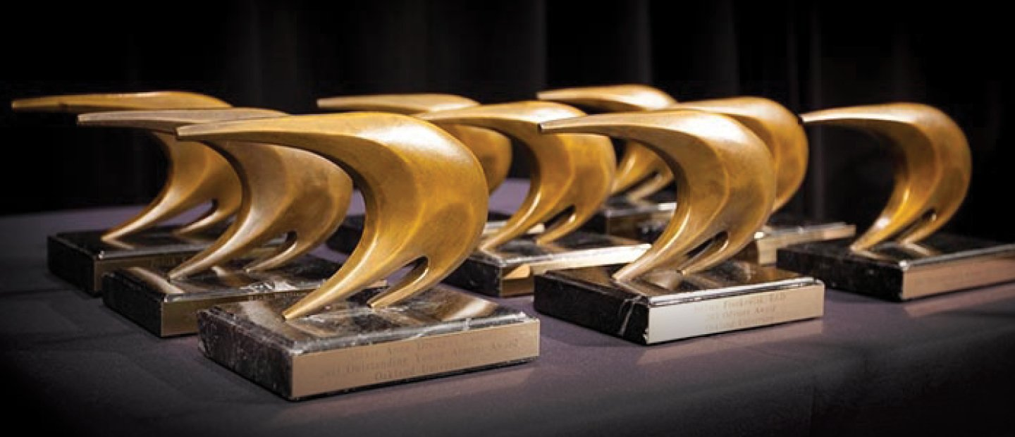 gold sail shaped awards lined up on a table
