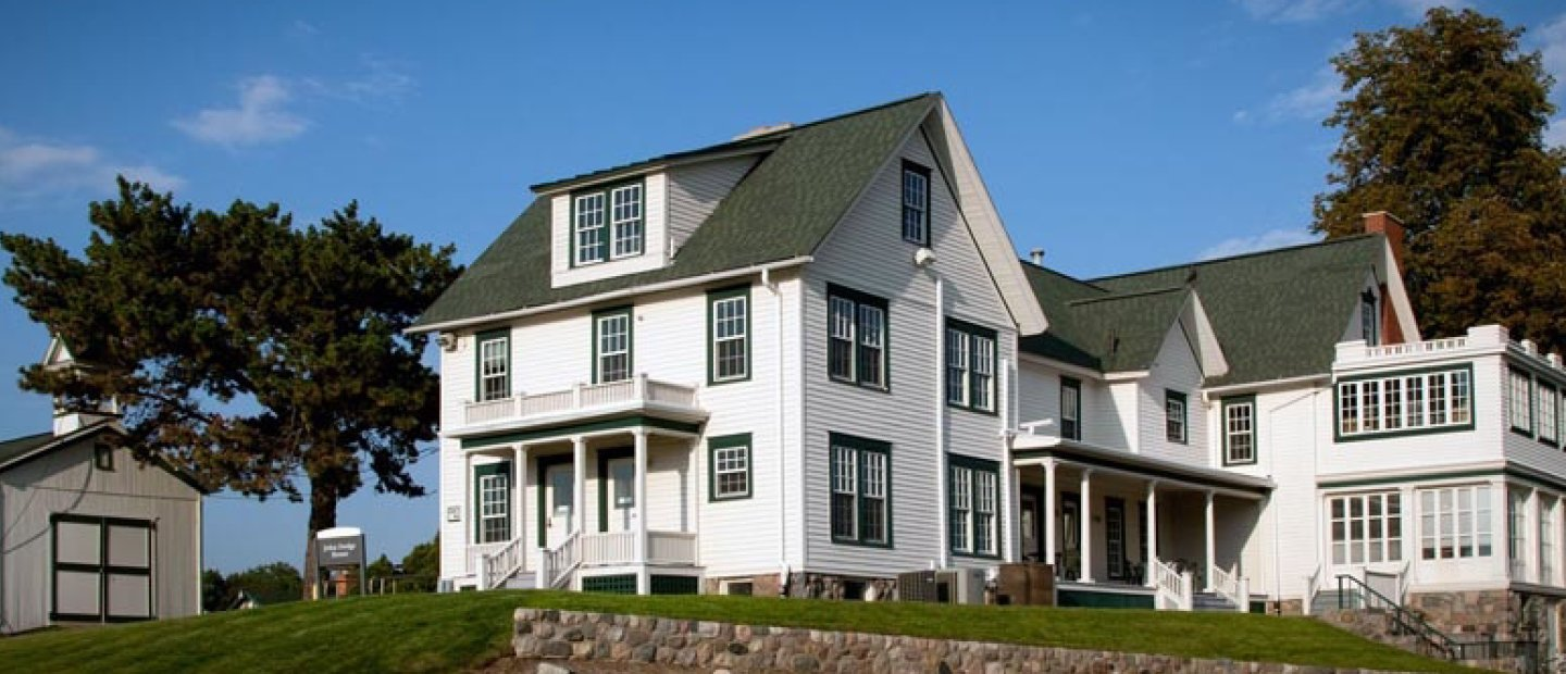 large white house with a green roof and trim