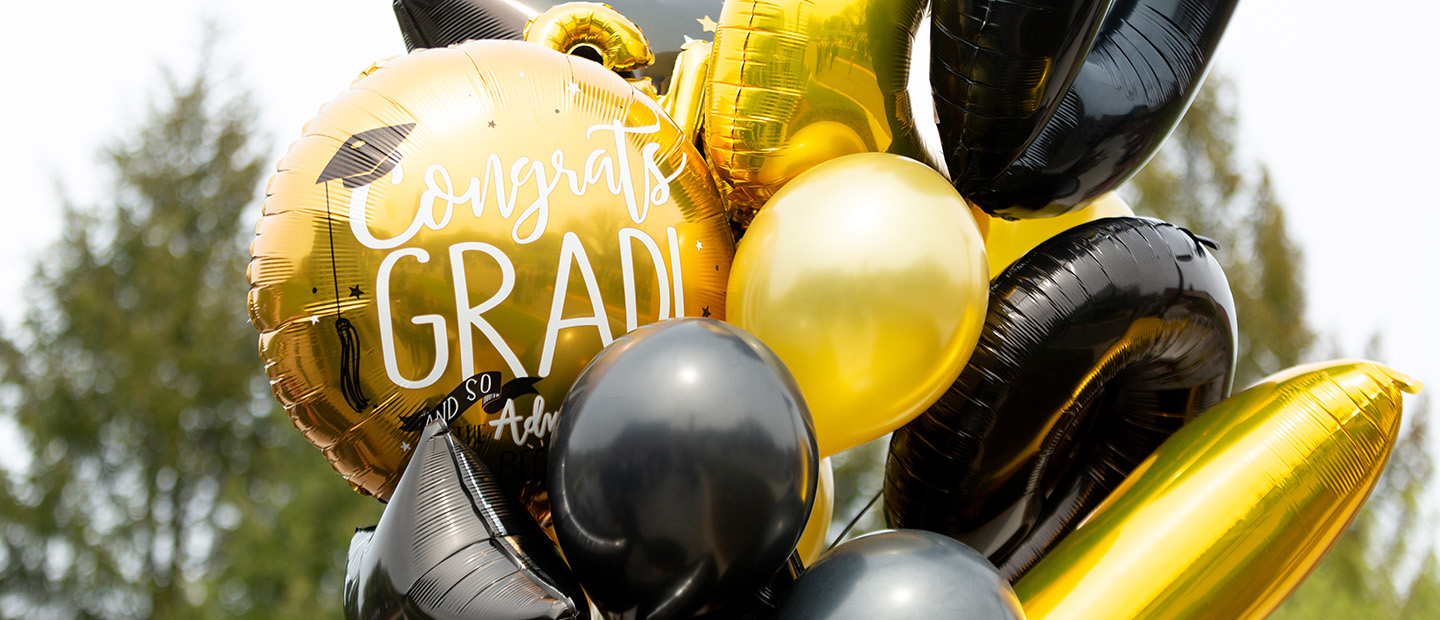 "A bunch of gold and black balloons, one that says ""Congrats Grad!"""