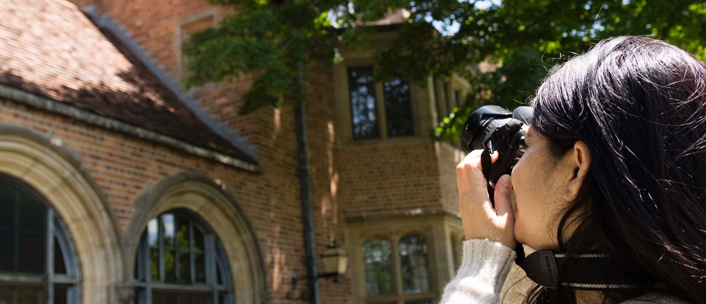 woman taking a photo of the exterior of a brick building