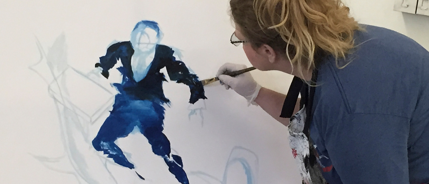 Female student painting a male figure in shades of blue.