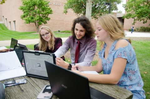 three students using laptops while seated at picnic table outside a school building