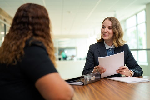 woman in business attire at desk smiling and holding papers talking to another woman