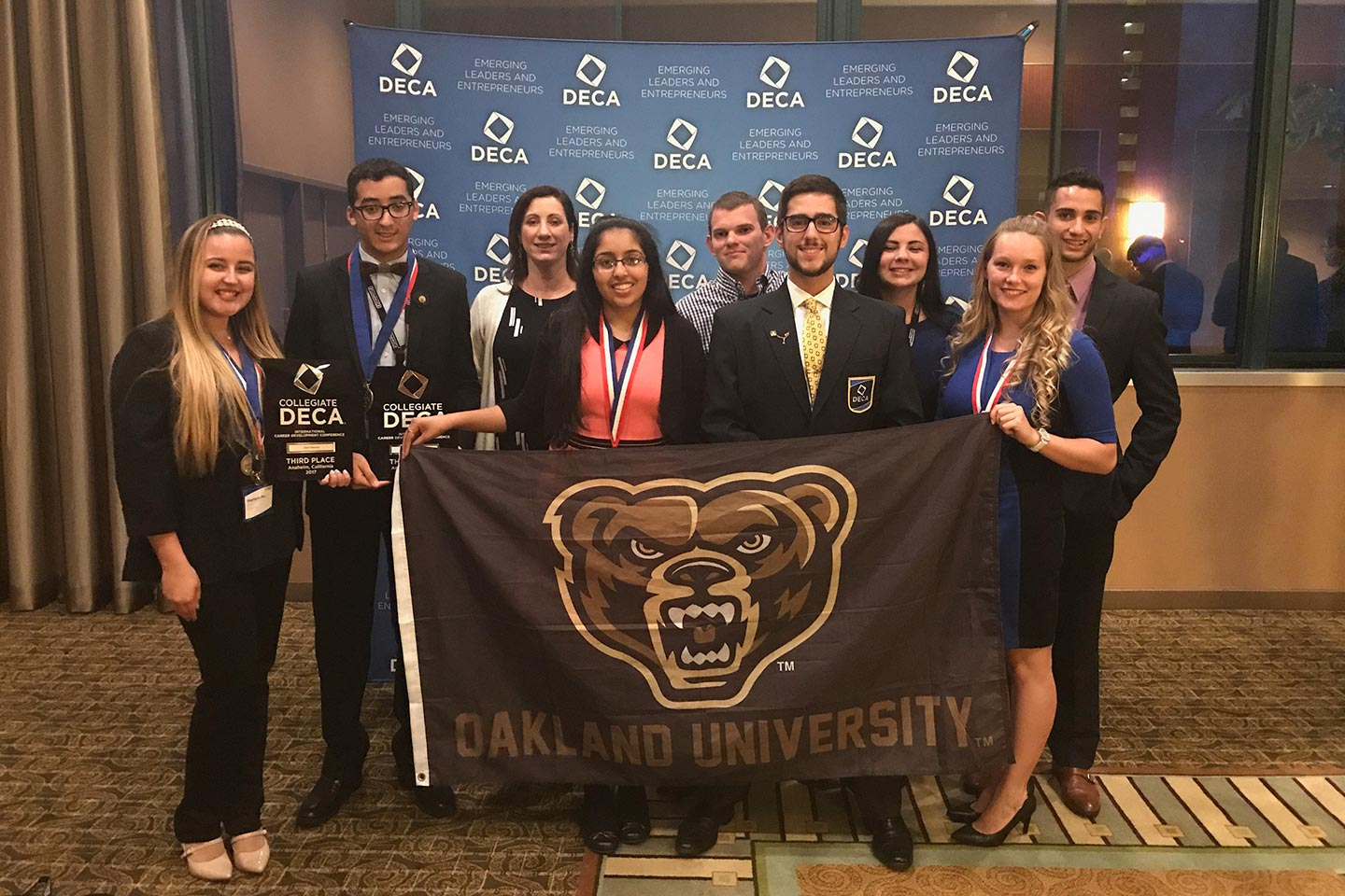 The OU DECA team holding awards and an OU Grizz flag