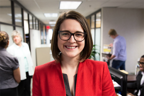 Caitlin Demsky, Ph.D. in a red jacket in an office