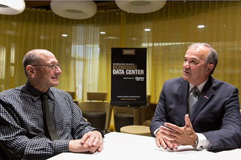Dr. Jonathan Silberman and Tom Kuslits seated at a table in front of a sign that reads Economic Data Center