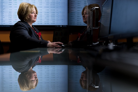 Woman in a business suit sitting in a dark room with a screen of data behind her.