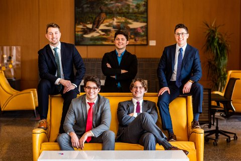 Five young men in suits, posing for a photo on yellow furniture.