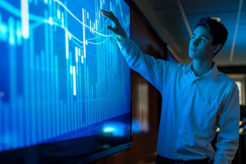 A young man pointing at data in a graph on a blue screen in front of him.