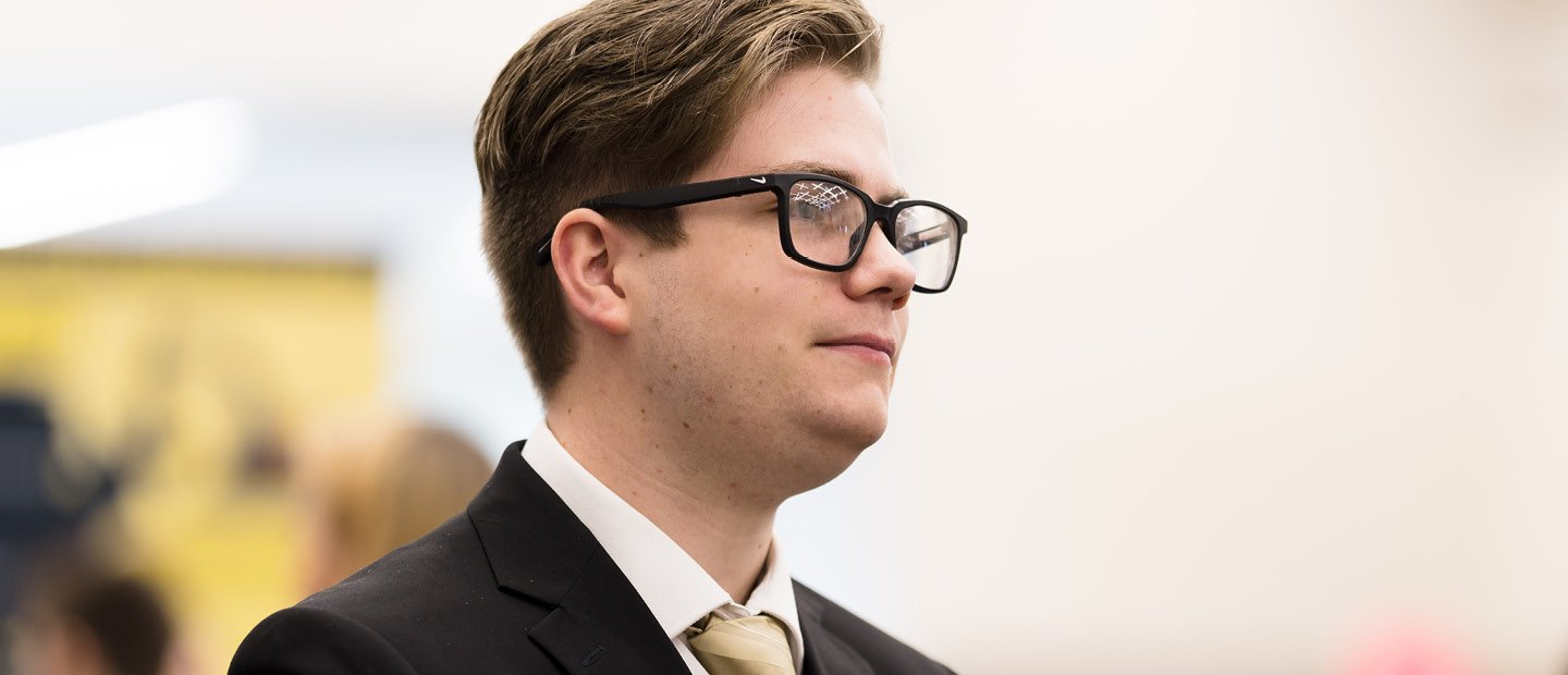 A profile photo of a young man in glasses and a black suit jacket with a gold tie.