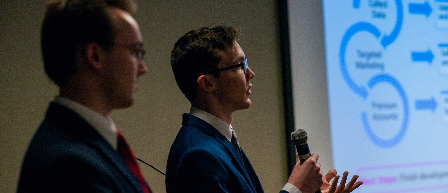 Two young men in suits, one holding a microphone, standing next to a projector screen.