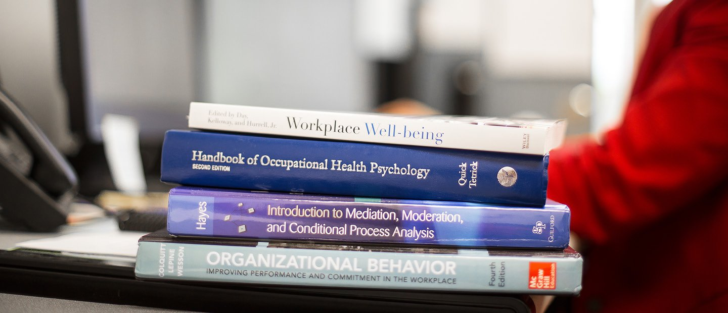 A stack of textbooks on the edge of a desk occupied by a person wearing red.