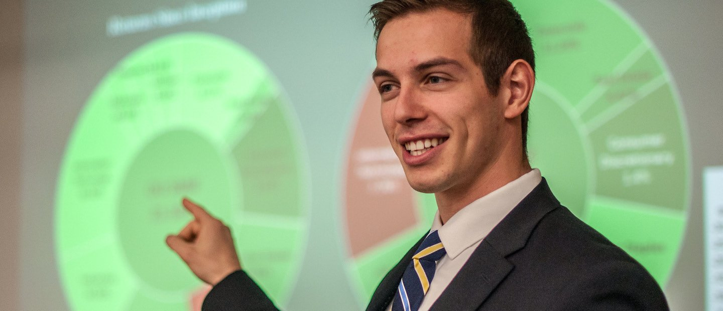 A young man in a suit, pointing to a neon green chart on a screen behind him.