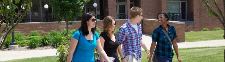 Four students outside residence hall, walkin, talking, spring / summer.