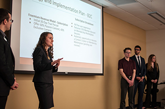 Business Scholars presenting at Case Competition. Female presenting before slides.