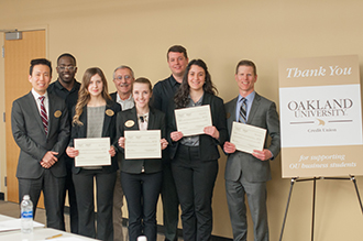 Winning Business Scholars Team in Case Competition. Five students with judges. Students holding award certificates.