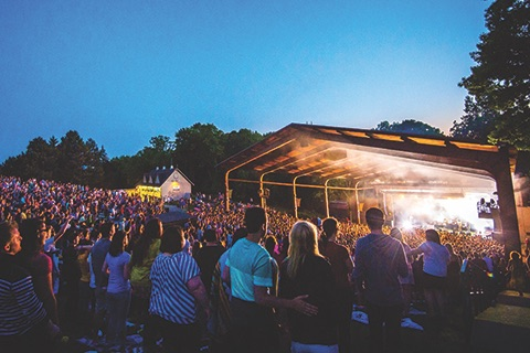 image of Meadow Brook Amphitheatre, an outdoor concert venue, depicting the stage with a band, at night, with a large crowd of people
