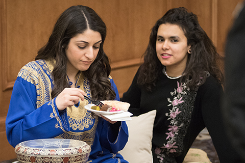image of two girls sitting on the ground, eating food, dressed in international wear
