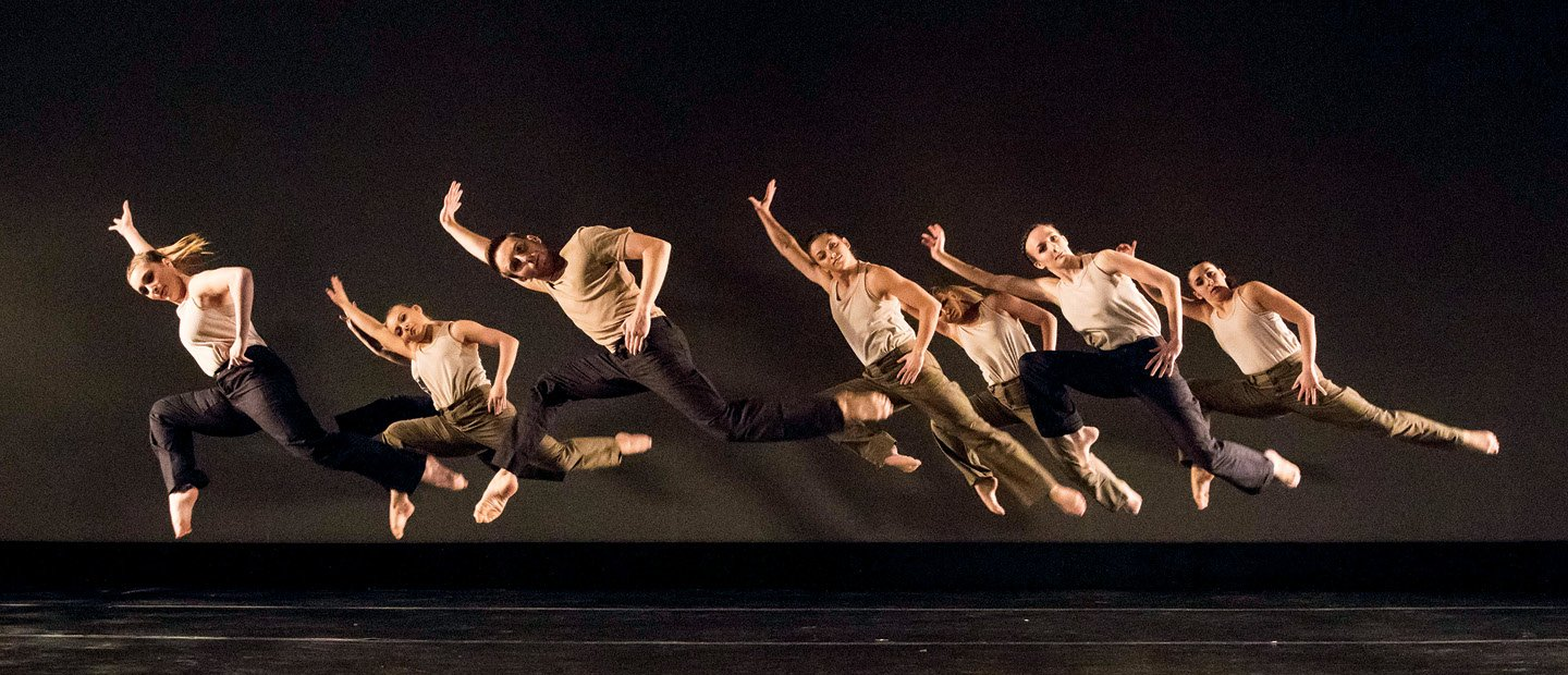 A group of dancers all leaping into the air, leaning right and extending their right arms and left legs.