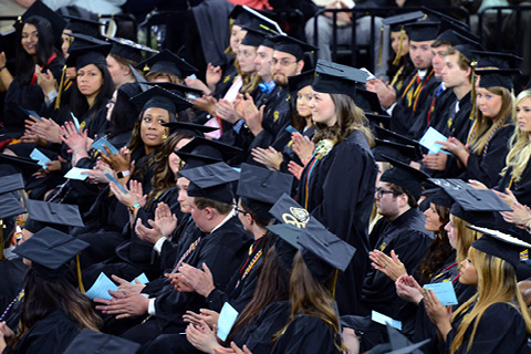Students in caps and gowns clapping at a commencement ceremony