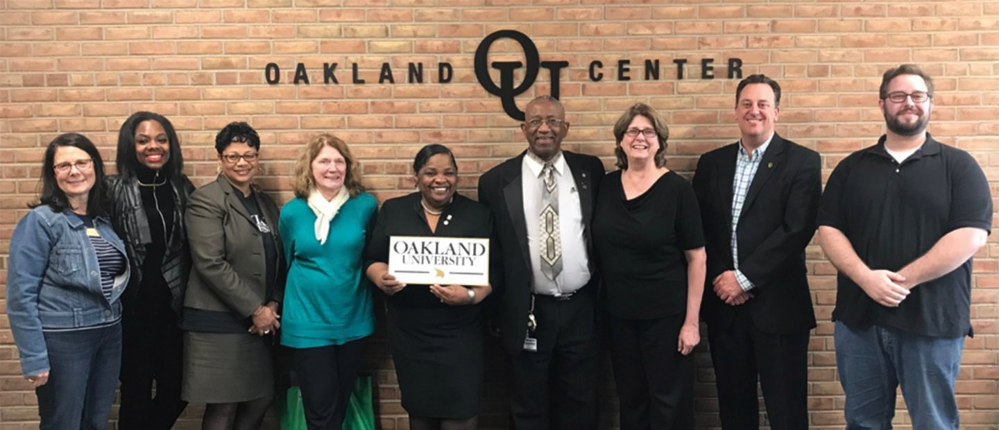 group of adults posing in front of a wall that says Oakland O U Center