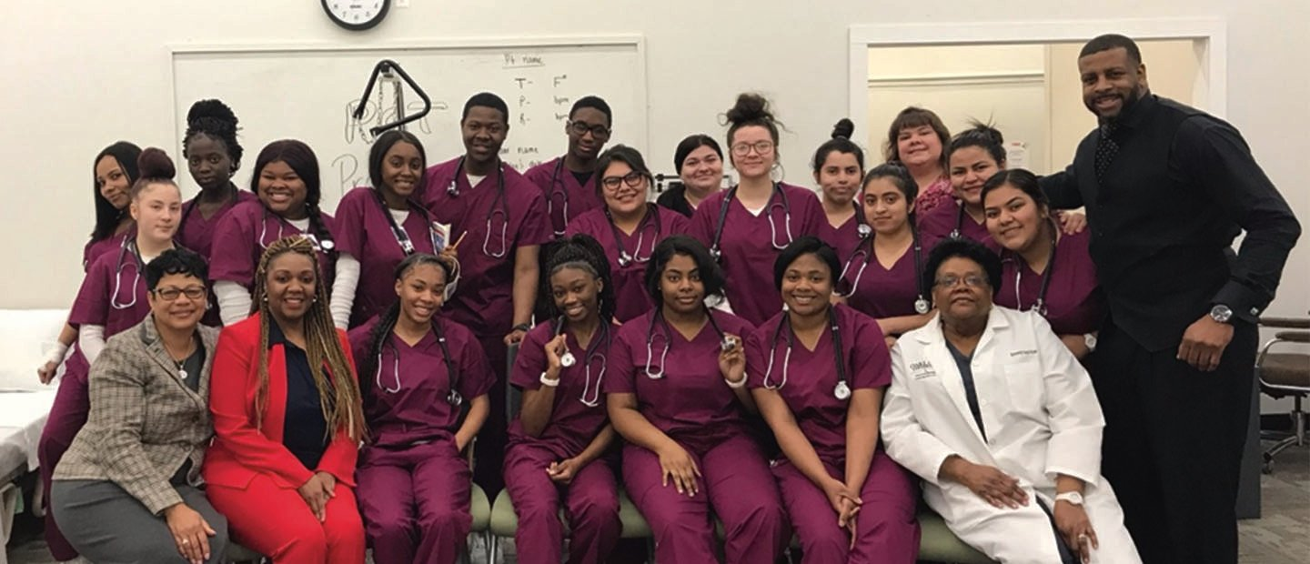 group of students in burgundy scrubs with stethoscopes around their necks, posing with instructors