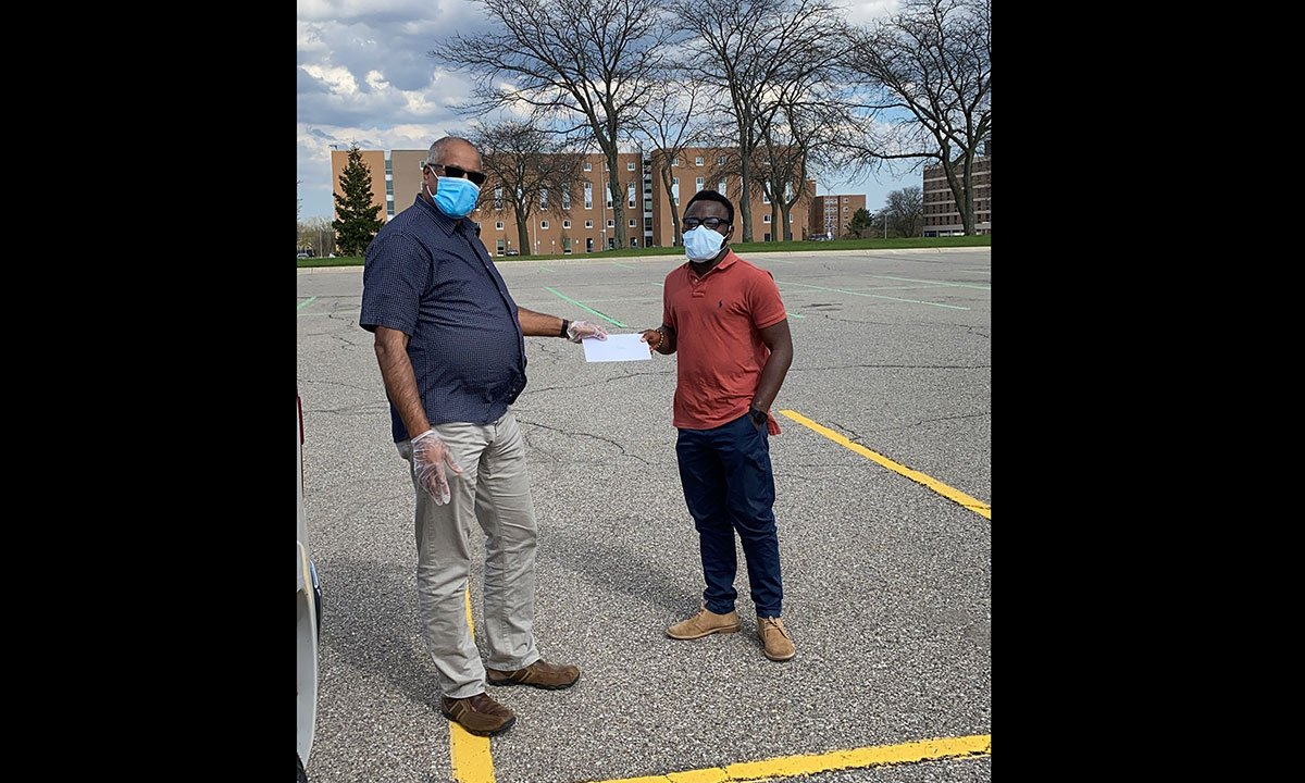 Two people wearing masks, standing in a parking lot.