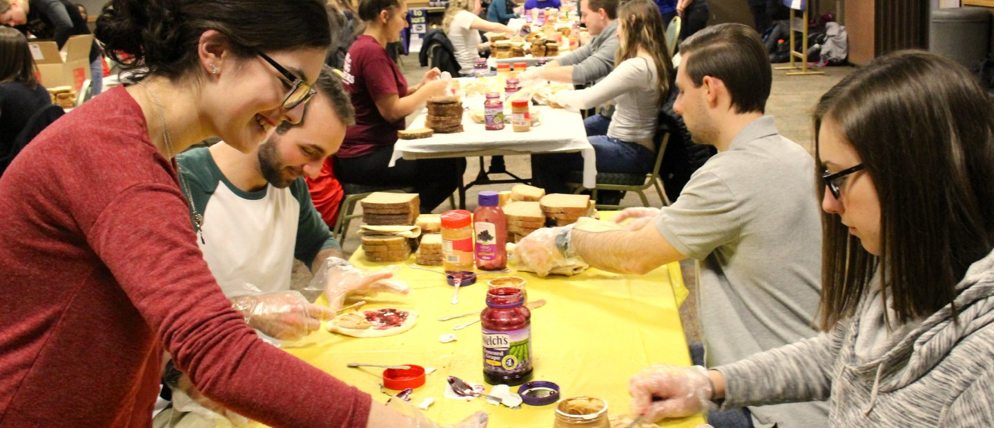 Students at tables making peanut butter and jelly sandwiches