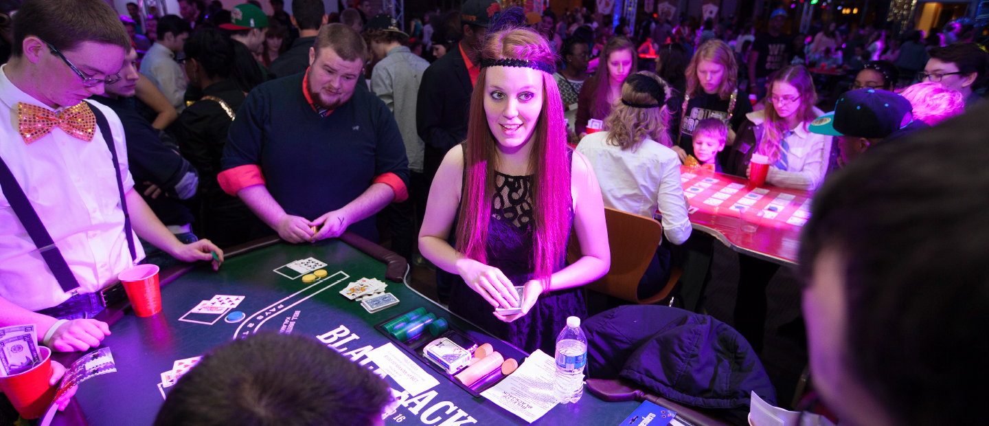 Student Program Board web banner image, a crowded room depicting a casino night, featuring a girl dressed as a flapper dealing cards to a table