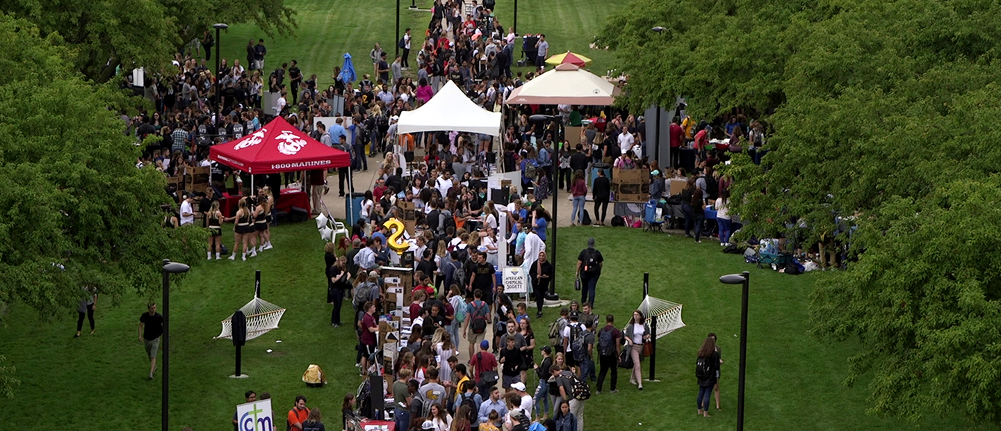 aerial view image of crowds of students and tents surrounded by trees