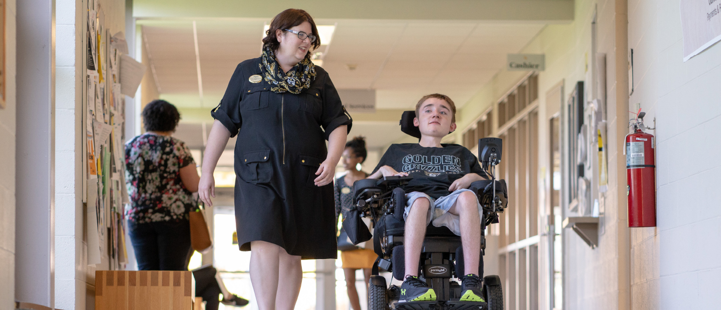 woman walking down a hallway with a young man in a wheelchair next to her