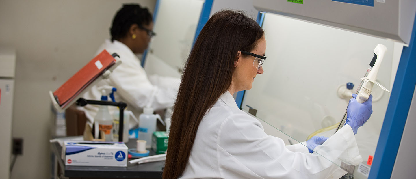 two women wearing white coats, using equipment in a lab