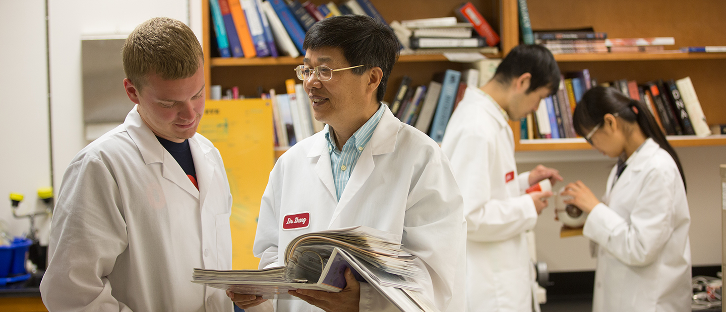 four people in white lab coats, standing in front of a book shelf, looking through a binder