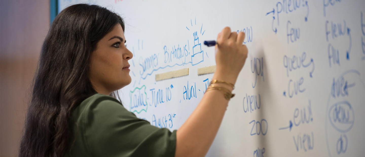 A woman writing on a white board with a blue marker.