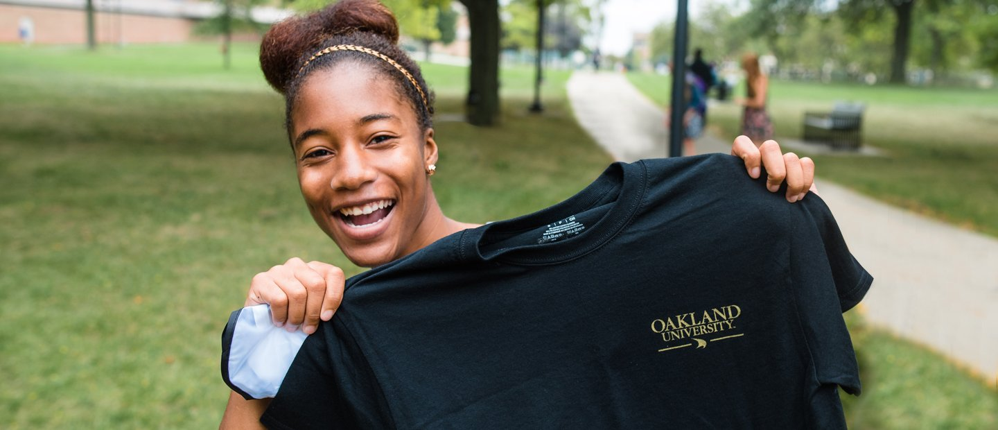 female student holding up a black t-shirt that has Oakland University printed on it