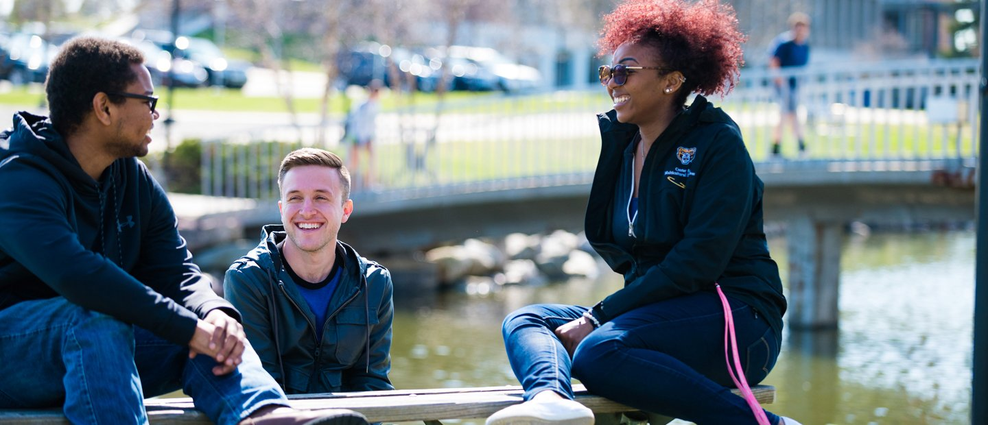 two male and one female O U student seated outside in front of a lake with a bridge in the background