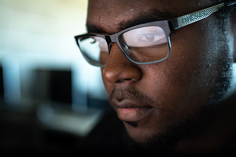 man wearing glasses that are reflecting text on a computer screen