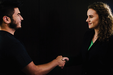 Man and woman dressed in black, shaking hands, against a black background