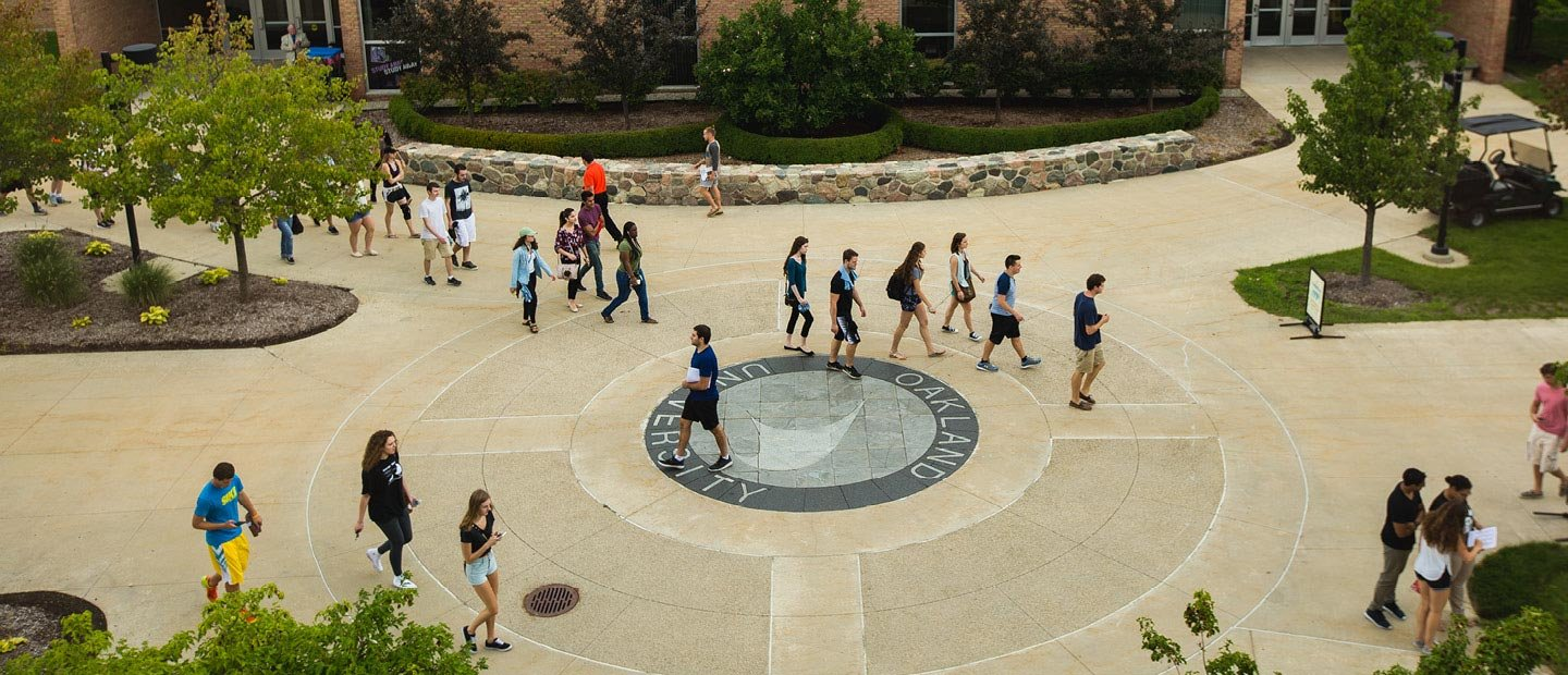 Students in a group walking across Oakland University's campus outdoors
