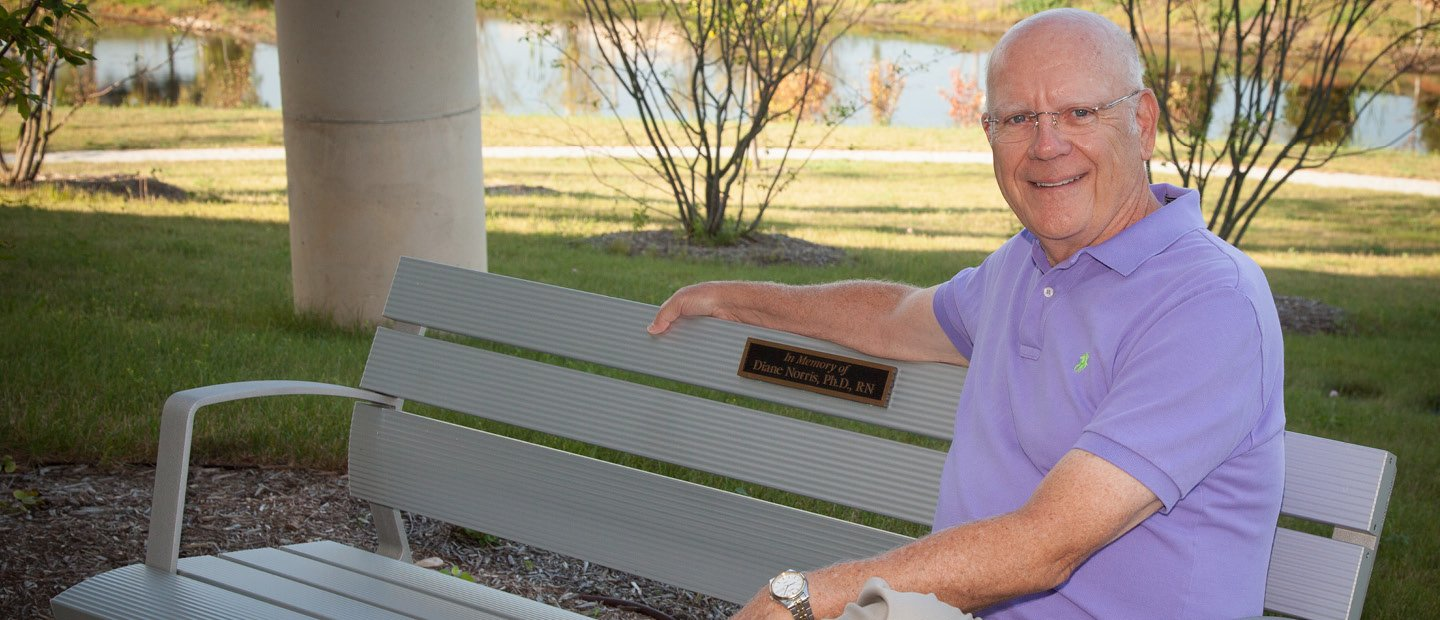 "man sitting on a bench with a plaque that says ""In Memory of Diane Norris, Ph.D., RN"""