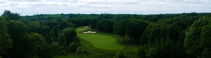 image of golf course greens in the woods from an aerial view