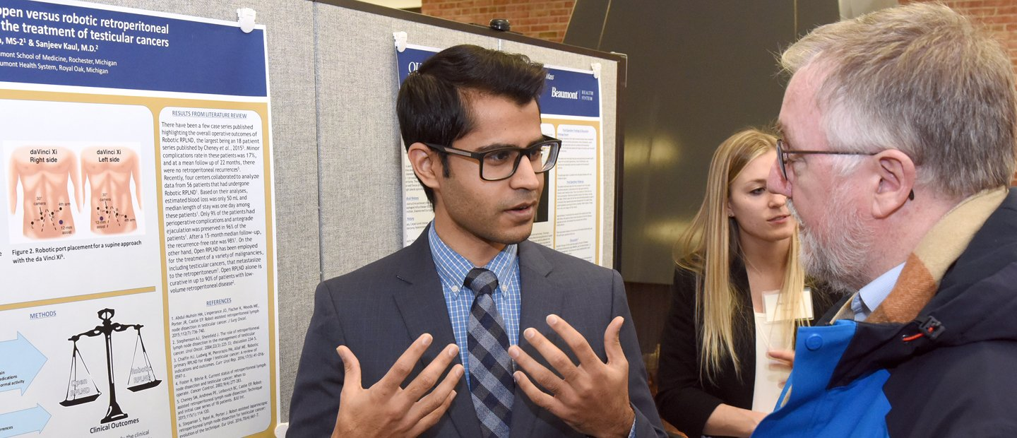 Student wearing a blue suit presenting his project to a professor