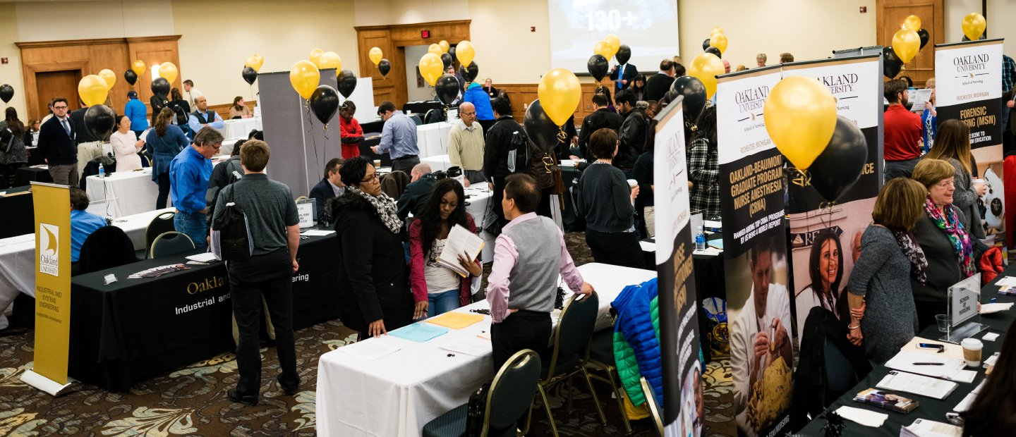 Students at an open house event with display tables, banners and black and gold balloons