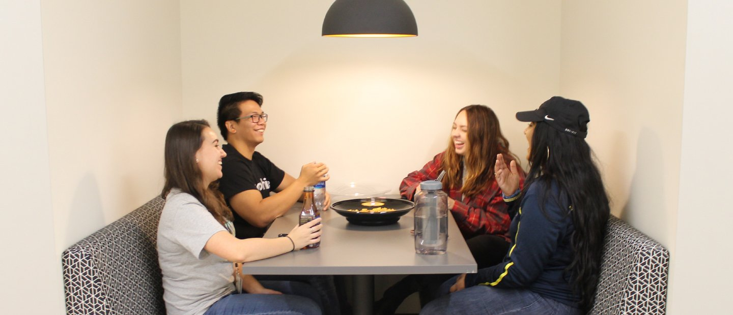 four students seated at a table with beverages and a bow of food in the middle