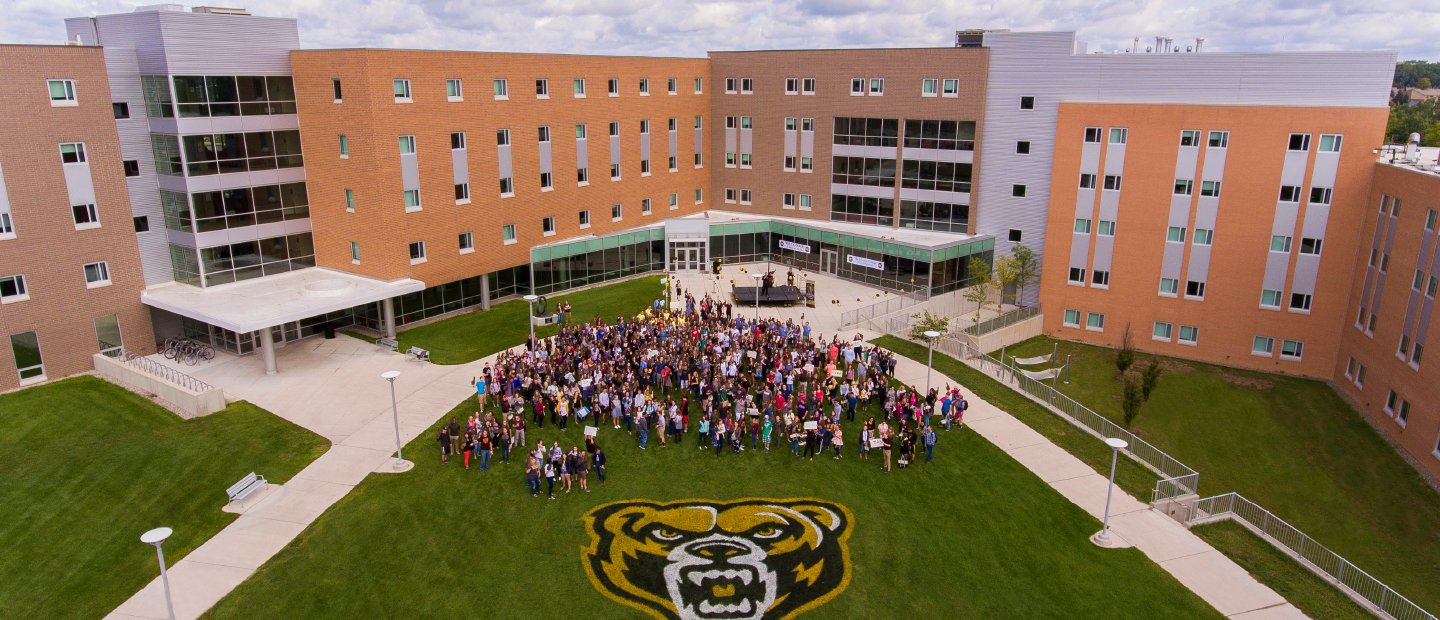 students in front of the Honors College building with the Grizz bear logo painted on the grass
