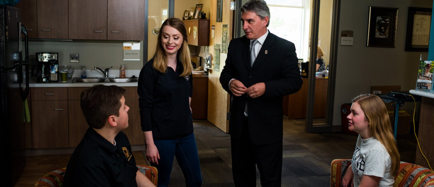 Honors college adviser and dean speaking to two students in an office