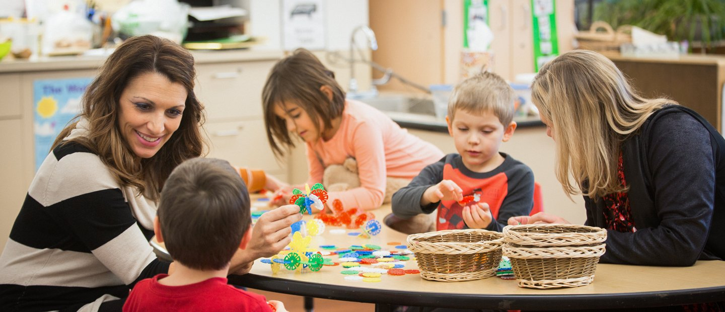 Two female teachers with three young students playing with colorful toys in a classroom.